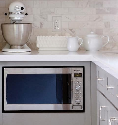 A neatly installed under counter microwave oven.